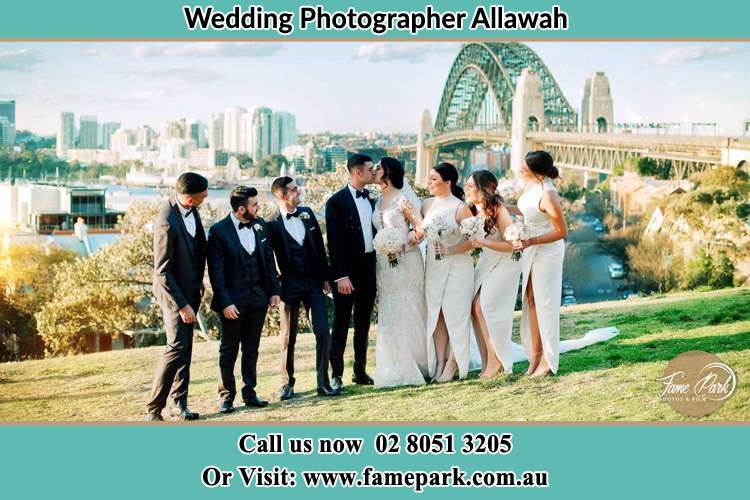 Photo of the Groom and the Bride kissing with their entourage near the bridge Allawah NSW 2218