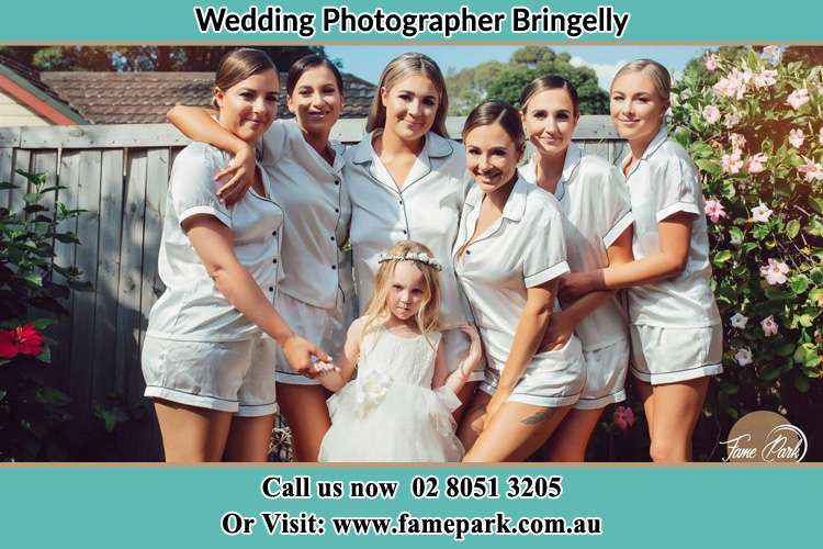 The Bride and the bridesmaids with the flower girl sticking a pose on camera Bringelly NSW 2556