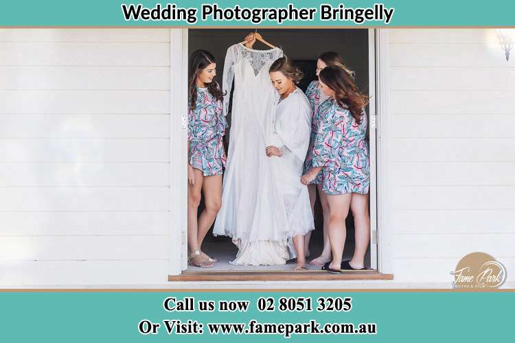 Photo of the Bride with her bridesmaids checking her gown Bringelly NSW 2556