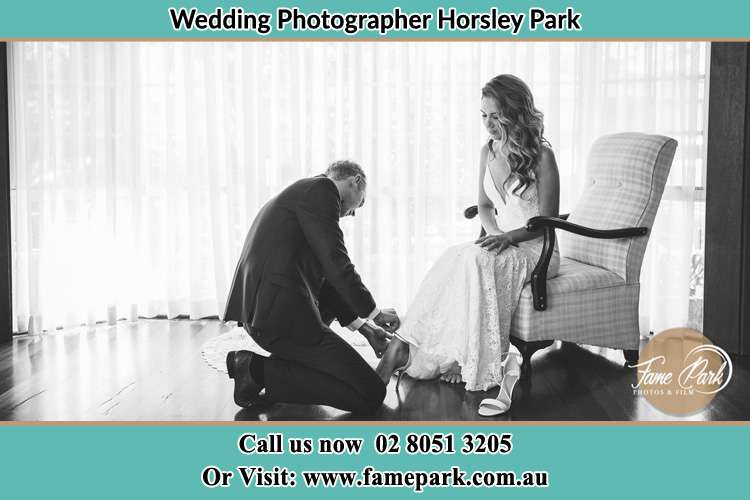 The Bride is being helped by the Groom trying to put on her shoes Horsley Park NSW 2175