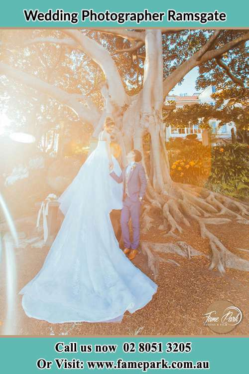 Photo of the Bride and the Groom looking each other besides the tree Ramsgate NSW 2217